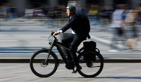 FILE PHOTO: A man rides an electric bicycle, also known as an e-bike, in downtown Milan, Italy, May 18, 2018. REUTERS/Stefano Rellandini