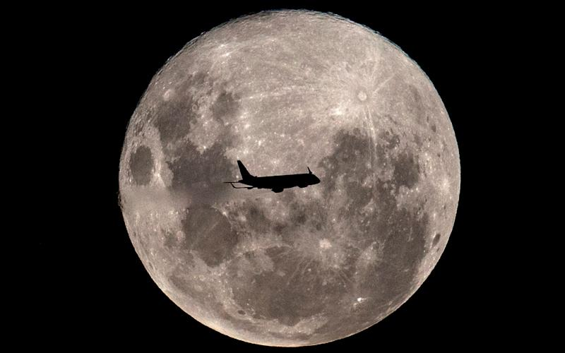 A plane passes in front of the super full moon, as seen from Buenos Aires on February 19, 2019 - AFP