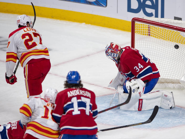 Calgary Flames' Josh Leivo (27) scores the third goal against Montreal Canadiens goaltender Jake Allen (34) during the third period of an NHL hockey game Wednesday, April 14, 2021 in Montreal. (Ryan Remiorz/Canadian Press via AP)