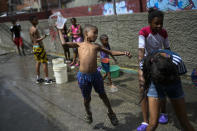 A boy prepares to playfully drench a friend with water during carnival celebrations in the Pinto Salinas neighborhood of Caracas, Venezuela, Monday, Feb. 15, 2021, amid the new coronavirus pandemic. (AP Photo/Matias Delacroix)