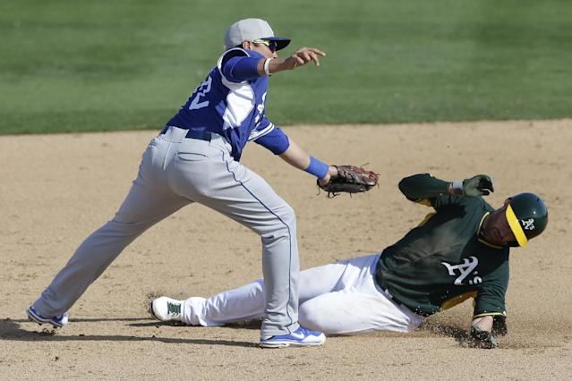 The Oakland Athletics' Jake Elmore, right, tries to avoid the tag as he is caught stealing second base as Los Angeles Dodgers shortstop Miguel Rojas, left, reaches for him during the sixth inning of a spring training baseball game Monday, March 3, 2014, in Phoenix. (AP Photo/Gregory Bull)