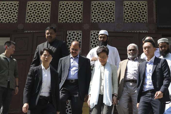 Hong Kong Chief Executive Carrie Lam, center, leaves a mosque in Hong Kong, Monday, Oct. 21, 2019. Lam and other officials apologized to leaders of the Kowloon Mosque after riot police sprayed the building's gate and some people nearby with a blue-dyed liquid from a water cannon as they tried to contain pro-democracy demonstrations Sunday. (AP Photo)