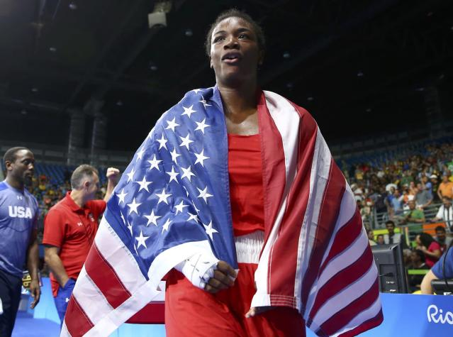 2016 Rio Olympics - Boxing - Final - Women's Middle (75kg) Final Bout 270 - Riocentro - Pavilion 6 - Rio de Janeiro, Brazil - 21/08/2016. Claressa Shields (USA) of USA wears her national flag as she celebrates after winning her bout. REUTERS/Peter Cziborra FOR EDITORIAL USE ONLY. NOT FOR SALE FOR MARKETING OR ADVERTISING CAMPAIGNS.
