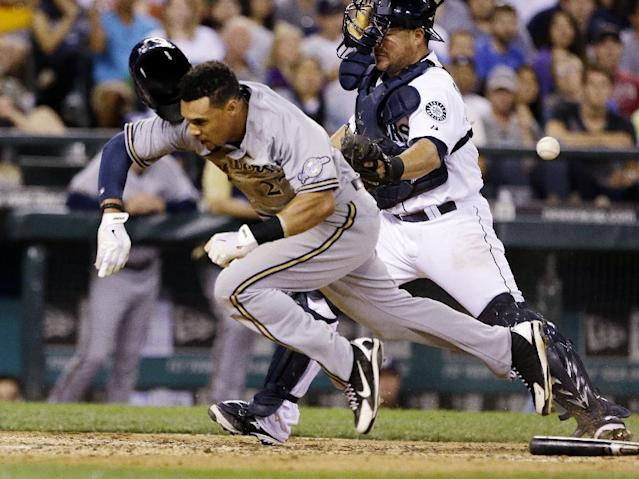 Milwaukee Brewers' Carlos Gomez, left, tumbles toward the ground after running into Seattle Mariners catcher Humberto Quintero, as the ball comes loose and Gomez scores in the seventh inning of a baseball game Saturday, Aug. 10, 2013, in Seattle. (AP Photo/Elaine Thompson)