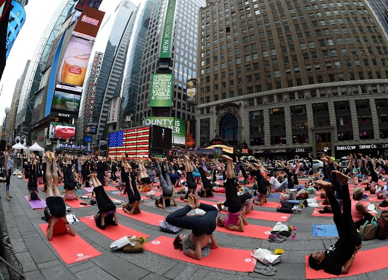 People practice yoga in New York's Times Square while celebrating the summer solstice on June 21, 2015 (AFP Photo/Don Emmert)