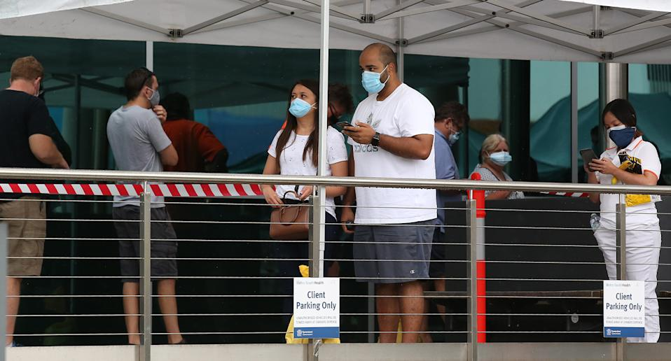 People wait in line in Brisbane while wearing face masks.