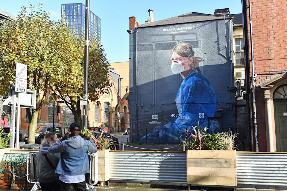 A mural depicting a health worker by artist Peter Barber in Manchester as the Government is preparing to impose stringent new coronavirus controls on 2.8 million people after talks with the local leaders for Greater Manchester failed to reach agreement. Leaders have been given until midday on Tuesday to reach a deal, or face unilateral Government action, after 10 days of negotiations failed to reach an agreement. (Photo by Jacob King/PA Images via Getty Images)