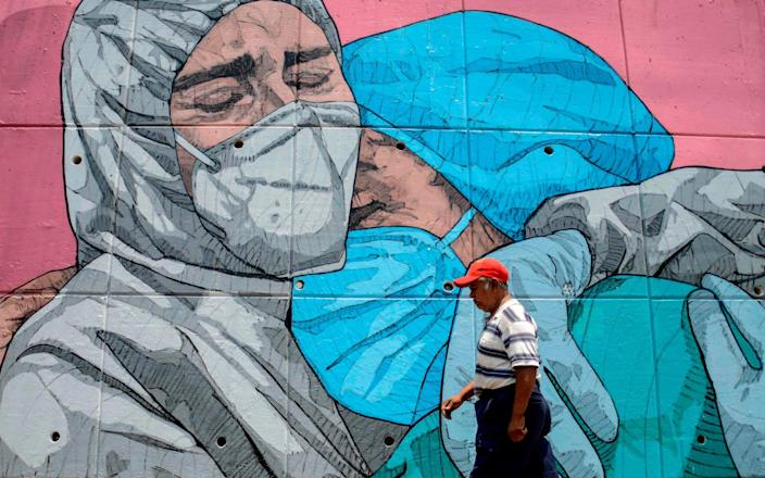 A man walks past a coronavirus-related mural, in Acapulco, Guerrero State, Mexico - FRANCISCO ROBLES/AFP