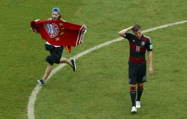 A fan runs on the pitch past Germany's Toni Kroos during their 2014 World Cup Group G soccer match at the Pernambuco arena in Recife June 26, 2014. REUTERS/Ruben Sprich (BRAZIL - Tags: SOCCER SPORT WORLD CUP TPX IMAGES OF THE DAY)