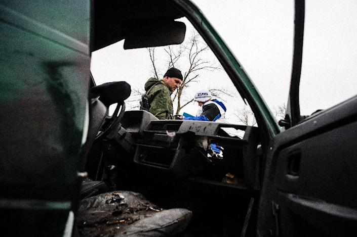 A pro-Russia rebel and an international observer of the OSCE stand next a destoyed car during an OSCE inspection tour near the village of Shirokino on March 30, 2015 (AFP Photo/Dimitar Dilkoff)