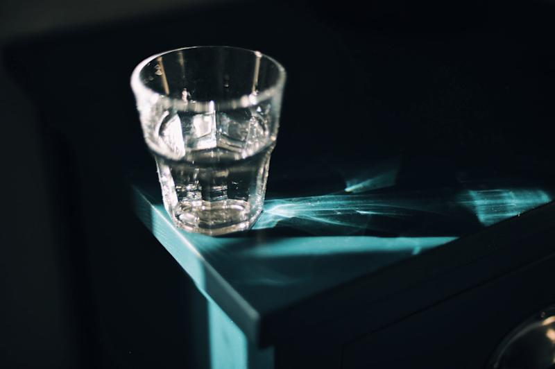 Glass of water in strong sunlight on bedside table