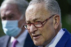 Schumer, wearing glasses, speaks at a news conference.