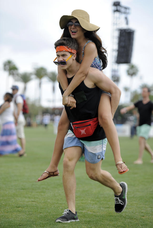 Dorian Danic, of Los Angeles, carries Lauren Saint on his back as they rush to catch the beginning of Kendrick Lamar's set during the first weekend of the 2012 Coachella Valley Music and Arts Festival, Friday, April 13, 2012, in Indio, Calif. (AP Photo/Chris Pizzello)