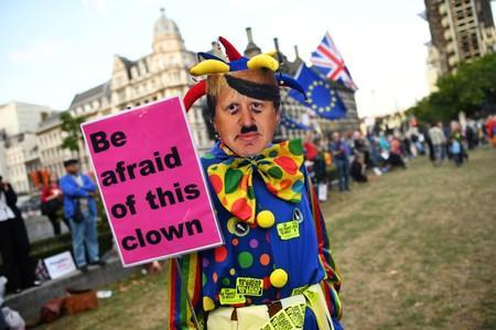 An anti-Brexit protester wearing a clown costume and a defaced mask depicting British Prime Minister Boris Johnson holds a placard outside the Houses of Parliament in London