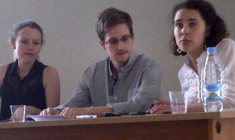 In this image provided by Human Rights Watch, NSA leaker Edward Snowden, center, attends a news conference at Moscow's Sheremetyevo Airport with Sarah Harrison of WikiLeaks, left, Friday, July 12, 2013. Snowden wants to seek asylum in Russia, according to a Parliament member who was among about a dozen activists and officials to meet with him Friday in the Moscow airport where he's been marooned for weeks. Duma member Vyacheslav Nikonov told reporters of Snowden's intentions after the meeting behind closed doors in the transit zone of Moscow's Sheremetyevo airport. (AP Photo/Human Rights Watch, Tanya Lokshina)