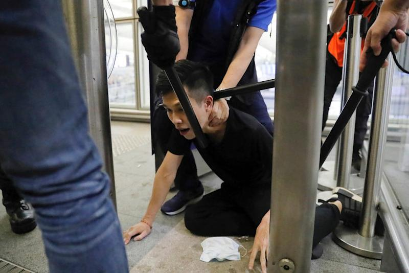 Policemen in riot gear arrest a protester during a demonstration at the Airport in Hong Kong, Tuesday, Aug. 13, 2019. (AP Photo/Kin Cheung)