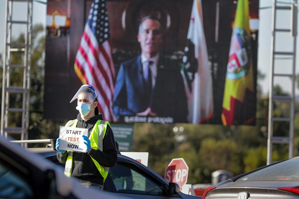 A volunteer holds a sign that says start test now while standing in front of a large video screen showing Mayor Eric Garcetti