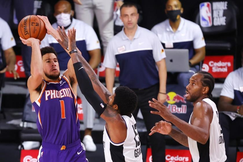 Phoenix Suns' Devin Booker shoots the game-winning basket over Los Angeles Clippers' Paul George.