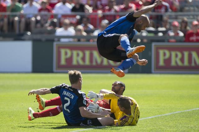 San Jose Earthquakes' Brandon Barklage vaults goalkeeper Jon Busch, right, as he smothers the ball as Toronto FC's Luke Moore, center, tries to convert a rebound under pressure from San Jose's Ty Harden during first half MLS action in Toronto on Saturday June 7, 2014. (AP Photo/The Canadian Press, Chris Young)