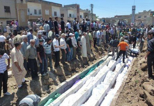 People watch the mass burial of the more than 100 victims of the Houla massacre in Syria on May 26. China on Wednesday restated its opposition to military intervention in Syria, as Russia sought to halt fresh UN Security Council action after the massacre of civilians sparked global fury