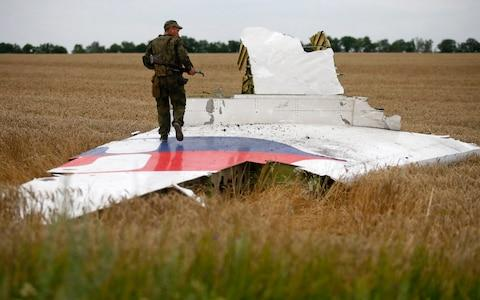 A separatist fighter stands on wreckage of the airliner near the village of Grabovo in July 2014 - Credit: MAXIM ZMEYEV/Reuters