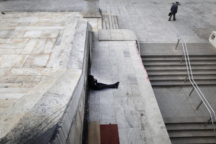 FILE - In this Tuesday, Jan. 22, 2013 file photo, a homeless man sits near the closed entrance of a Metro station in central Syntagma square during a strike held by the unions of metro services in Athens. Researchers from Greece's largest labor union, the GSEE, say the country's three-year crisis has left nearly two-thirds of private sector employees without receiving their regular salaries. GSEE has called a general strike for Feb. 20. (AP Photo/Petros Giannakouris, File)