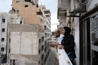 Nasia Abdullah Ali,36, and her brother Malik stand on a damaged balcony at home, in Benghazi