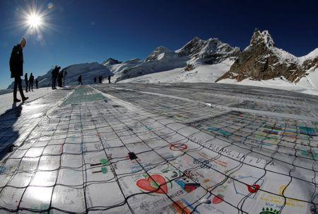 A general view shows 100,000 postcards with messages against climate change, sent by young people from all over the world and stuck together to break the Guinness World Record of the biggest postcard on the Jungfraufirn, the upper part of Europe's longest glacier, the Aletschgletscher, near Jungfraujoch, Switzerland November 16, 2018. REUTERS/Arnd Wiegmann