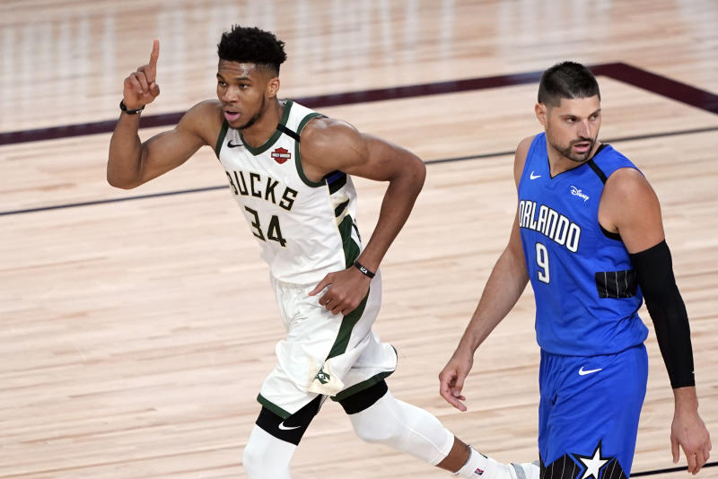 Milwaukee Bucks' Giannis Antetokounmpo (34) celebrates after a dunk as Orlando Magic's Nikola Vucevic (9) looks back during the first half of an NBA basketball first round playoff game Saturday, Aug. 29, 2020, in Lake Buena Vista, Fla. (AP Photo/Ashley Landis)