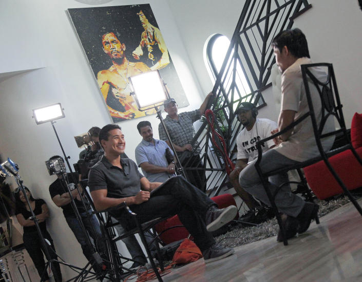 """Manny Pacquiao, right, world champion boxer and Filipino congressman, speaks about his views on same-sex marriage, and other subjects, during the taping of a segment of the """"Extra"""" entertainment TV show with Mario Lopez, seated left, at his home in Los Angeles on Wednesday, May 16, 2012. (AP Photo/Reed Saxon)"""