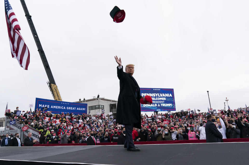 President Donald Trump throws a hat to supporters as he arrives to speak at a campaign rally at Altoona-Blair County Airport, Monday, Oct. 26, 2020, in Martinsburg, Pa. (AP Photo/Alex Brandon)