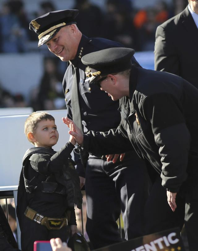 """Five-year-old leukemia survivor Miles, dressed as """"Batkid"""" high fives with San Francisco Fire Department chief Joanne Hayes-White (R) as with police chief Greg Suhr (C) watches during a ceremony as part of a day arranged by the Make- A - Wish Foundation in San Francisco, California November 15, 2013. The young cancer survivor will be treated to various super hero scenarios including receiving a commendation at San Francisco City Hall. REUTERS/Robert Galbraith (UNITED STATES - Tags: SOCIETY ENTERTAINMENT)"""