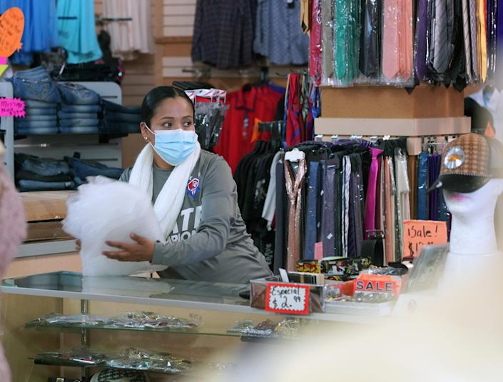 Esthela Cisneros works at Ensueño Boutique in downtown Dodge City, Kan. Her boss, Andres Lima, said he's required staff and customers to wear masks inside the store for months.