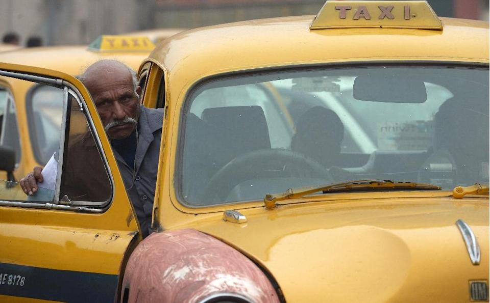 Taxi drivers waiting for fares in black and yellow Ambassador taxis have been a familiar sight in the Indian capital of New Delhi for generations (AFP Photo/Dibyangshu Sarkar)