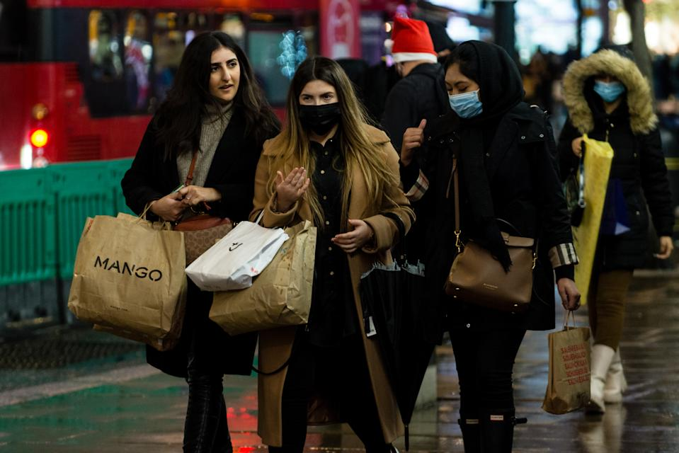 Shoppers wear face masks as they walk in Oxford Street, ahead of the new Tier-4 restriction measures, on December 19, 2020 in London, England.  Britain's Prime Minister Boris Johnson says Christmas gatherings cannot go ahead and non-essential shops must close in London and much of southern England as he imposed a new, higher level of coronavirus restrictions to curb rapidly spreading infections. (Photo by Maciek Musialek/NurPhoto via Getty Images)