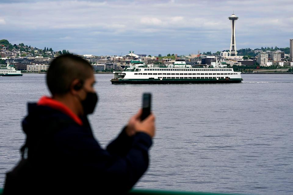 A passenger on a Washington state ferry with the Space Needle behind him