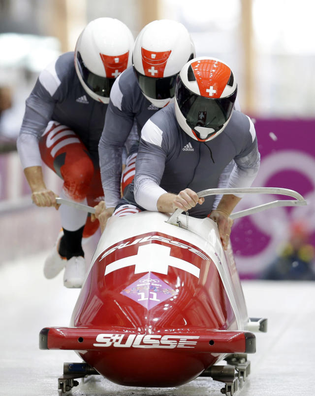 The team from Switzerland SUI-1, with Beat Hefti, Alex Baumann, Juerg Egger and Thomas Lamparter, start their third run during the men's four-man bobsled competition final at the 2014 Winter Olympics, Sunday, Feb. 23, 2014, in Krasnaya Polyana, Russia. (AP Photo/Natacha Pisarenko)