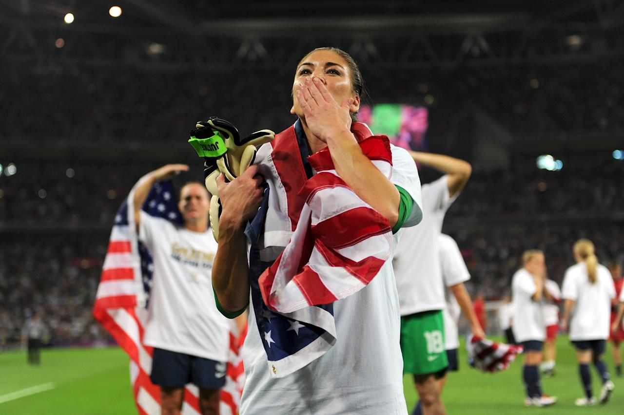 LONDON, ENGLAND - AUGUST 09:  Hope Solo #1 of the United States celebrates with the American flag after defeating Japan by a score of 2-1 to win the Women's Football gold medal match on Day 13 of the London 2012 Olympic Games at Wembley Stadium on August 9, 2012 in London, England.  (Photo by Michael Regan/Getty Images)