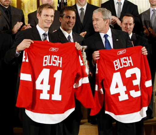 President Bush, right, holds up a jersey with players, Nicklas Lidstrom, from Sweden, left, and Chris Chelios, center, while on stage during a ceremony honoring the 2008 NHL Stanley Cup Hockey Champions the Detroit Red Wings in the East Room of the White House, Tuesday, Oct. 14, 2008 in Washington. (AP Photo/Pablo Martinez Monsivais)