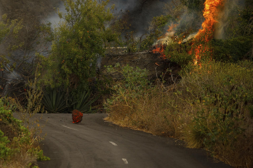 A molten rock from volcano lava sits in the middle of a road near El Paso on the island of La Palma in the Canaries, Spain, Monday, Sept. 20, 2021. Giant rivers of lava are tumbling slowly but relentlessly toward the sea after a volcano, seen in the backround, erupted on a Spanish island off northwest Africa. The lava is destroying everything in its path but prompt evacuations helped avoid casualties after Sunday's eruption. (Kike Rincon, Europa Press via AP)