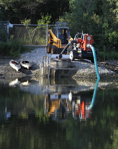 The pump at Meyers Lake continues to remove water from the lake as the search continues for Elizabeth Collins, 8, and her cousin Lyric Cook-Morrissey, 10, Wednesday, July 18, 2012, in Waterloo, Iowa. (AP Photo/Waterloo Courier, Matthew Putney)