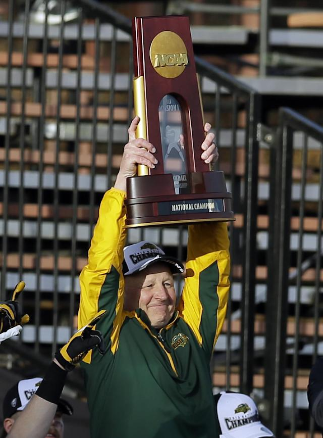 North Dakota State head coach Craig Bohl holds up the trophy as he celebrates winning the FCS championship NCAA college football game against Towson, Saturday, Jan. 4, 2014, in Frisco, Texas. NDSU won 35-7. (AP Photo/Tony Gutierrez)