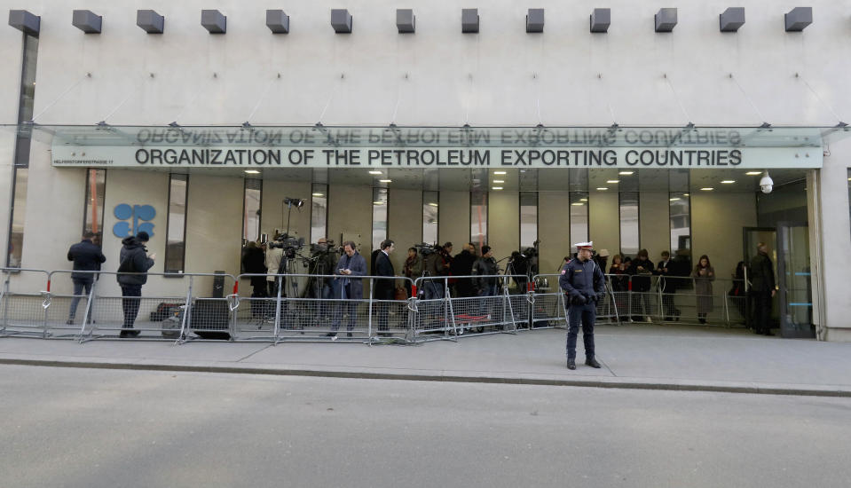 People stand in front of the headquarters of the Organization of the Petroleum Exporting Countries, OPEC, in Vienna, Austria, Thursday, March 5, 2020. (AP Photo/Ronald Zak)