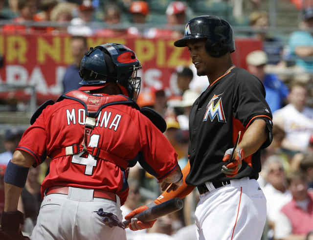Miami Marlins' Giancarlo Stanton, right, talks with St. Louis Cardinals catcher Yadier Molina after breaking his bat on a line out in the first inning of an exhibition spring training baseball game, Tuesday, March 25, 2014, in Jupiter, Fla. (AP Photo/David Goldman)