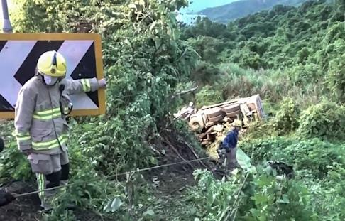 The driver of the truck, which plunged 30 metres down a slope, was rescued and taken to hospital. Photo: RTHK