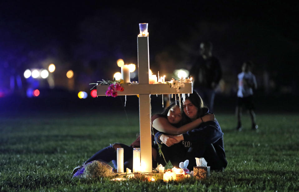 FILE - In this Feb. 15, 2018 file photo, people comfort each other as they sit and mourn at one of seventeen crosses, after a candlelight vigil for the victims of the shooting at Marjory Stoneman Douglas High School, in Parkland, Fla. Sorrow is reverberating across the country Sunday, Feb. 14, 2021, as Americans joined a Florida community in remembering the 17 lives lost three years ago in the Parkland school shooting massacre. President Joe Biden used the the occasion to call on Congress to strengthen gun laws, including requiring background checks on all gun sales and banning assault weapons. (AP Photo/Gerald Herbert, File)