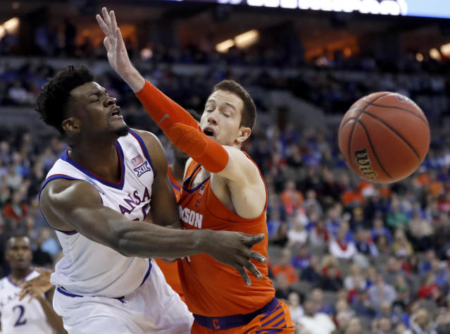 Kansas' Udoka Azubuike, left, passes around Clemson's David Skara during the first half of a regional semifinal game in the NCAA men's college basketball tournament Friday, March 23, 2018, in Omaha, Neb. (AP Photo/Nati Harnik)