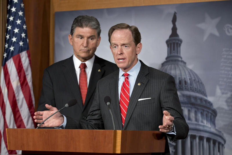 Democratic Sen. Joe Manchin of West Virginia, left, and Republican Sen. Patrick Toomey of Pennsylvania, right, announce that they have reached a bipartisan deal on expanding background checks to more gun buyers, at the Capitol in Washington in April 2013. A bipartisan gun control deal by Toomey and Manchin inspired Senate conservatives to drop their filibuster plans, even though many Republicans who allowed the legislation to advance said they were unlikely to vote for its passage in the end. (AP Photo/J. Scott Applewhite, File)