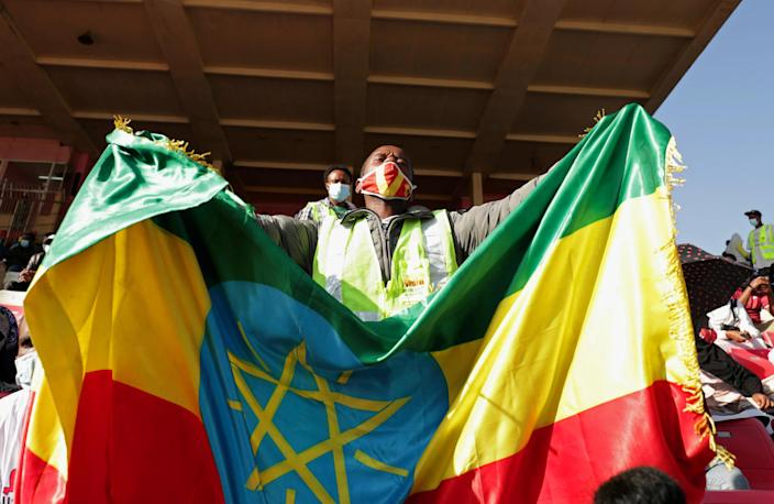 A volunteer holds an Ethiopian flag during a blood donation ceremony for the injured members of Ethiopia's National Defense Forces fighting against Tigray's special forces on the border between Amhara and Tigray, at the stadium in Addis Ababa, Ethiopia, November 12, 2020. / Credit: Reuters/Tiksa Negeri