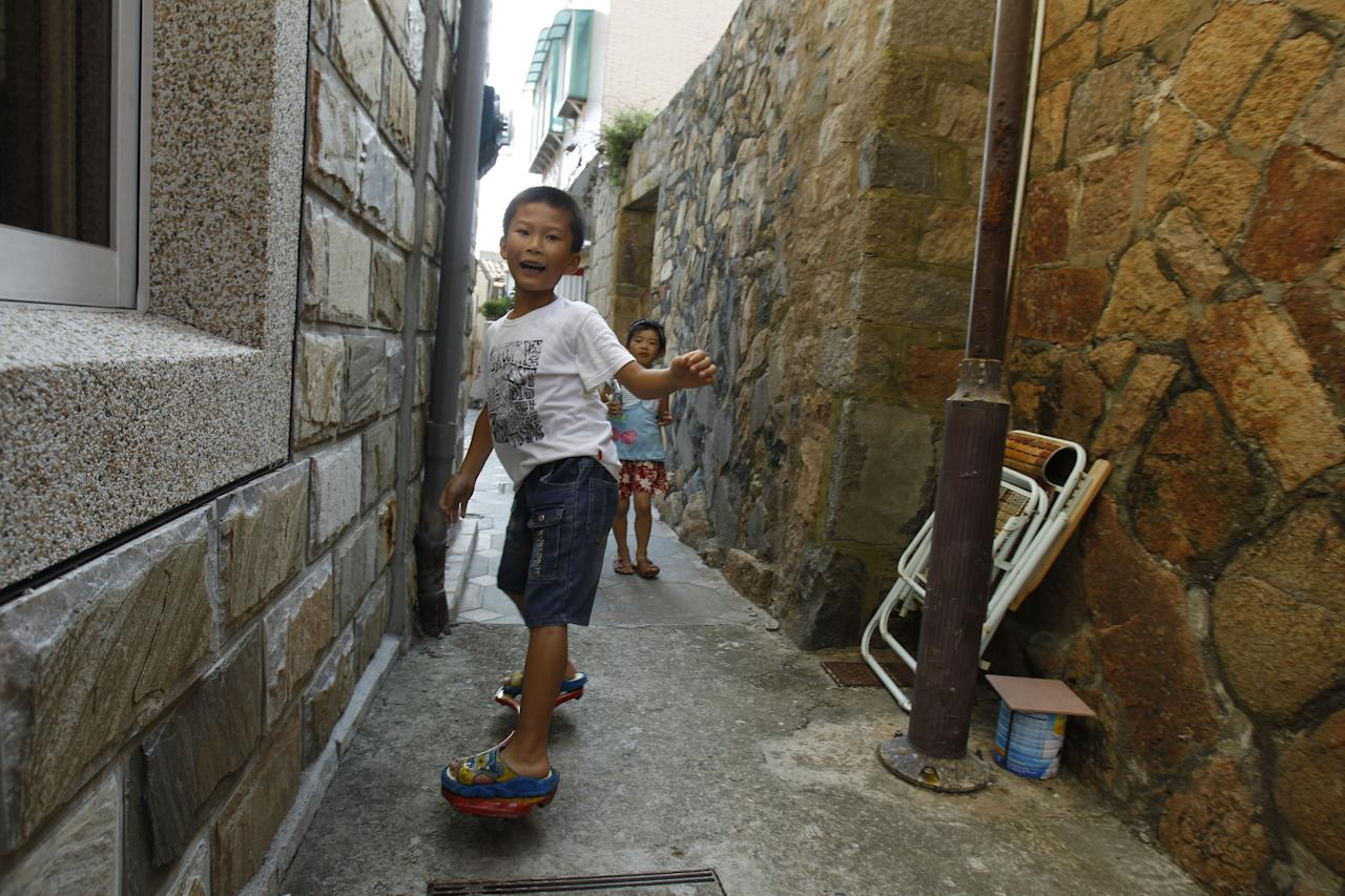In this Aug. 20, 2012 photo, children play in the empty stone houses of Beigan in the Matsu island group, off northern Taiwan. In early July some 3,000 Matsu residents voted 57 to 43 to permit casino gambling. Their votes were clearly influenced by the promises of not only a casino, but also a tourist resort, expanded airport, roadway infrastructure, a university, and perhaps most alluring of all, a monthly payment of 80,000 New Taiwan dollars ($2,666) for every resident. (AP Photo/Wally Santana)